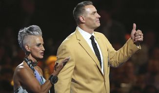 Brenda, left, and Kurt Warner wave to the crowd after Kurt received his gold jacket during the Pro Football Hall of Fame Festival Enshrinees' Gold Jacket Dinner at the Canton Memorial Civic Center in Canton, Ohio, Friday, Aug. 4, 2017. (Scott Heckel/The Canton Repository via AP) ** FILE **