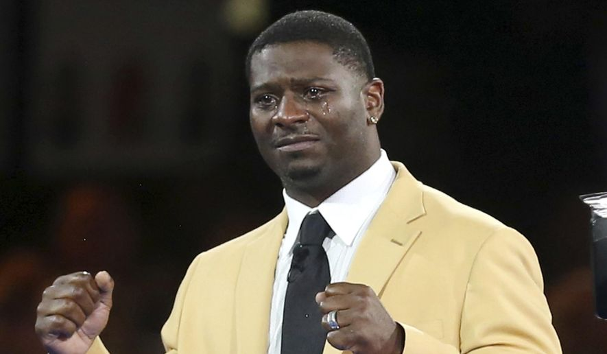 Tears run down the face of LaDainian Tomlinson as he reacts to the crowd after receiving his gold jacket during the Pro Football Hall of Fame Festival Enshrinees' Gold Jacket Dinner at the Canton Memorial Civic Center in Canton, Ohio, Friday, Aug. 4, 2017. (Scott Heckel/The Canton Repository via AP)