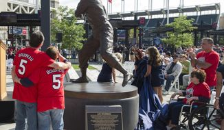 The children of Cleveland Indians Hall of Fame manager and player Lou Boudreau, Lou Boudreau Jr. left, Barbara Golaszewski, Sharon McLain, in wheelchair and Jim Boudreau view the newly unveiled statue of Boudreau at Progressive Field before a baseball game against the New York Yankees in Cleveland, Saturday, Aug. 5, 2017. (AP Photo/Phil Long)