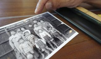 "In this Saturday, Aug. 5, 2017, photo, Kim Ji Nho, a pro-Pyongyang ethnic Korean who was born in Hiroshima, shows his only family photo taken in 1963 with him, third from right in the back, and his mother, top left, during an interview with The Associated Press in Hiroshima, western Japan. Kim, 71, is a ""hibakusha,"" or atomic-bomb survivor, who was exposed to radiation when his mother, pregnant with him, went to the ruins of the city to search for a daughter who went missing in the blast. ""We 'hibakusha' and our groups share a clear goal, which is to abolish nuclear weapons from the world,"" Kim said. ""Nuclear weapons should never be used."" (AP Photo/Mari Yamaguchi)"
