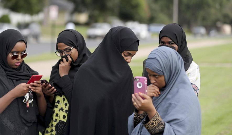 People make phone calls as law enforcement investigate an explosion at the Dar Al-Farooq Islamic Center in Bloomington, Minn., on Saturday, Aug. 5, 2017.   Bloomington police Chief Jeff Potts said Saturday that investigators are trying to determine the cause of the blast. Authorities say the explosion damaged one room but it didn't hurt anyone. (David Joles/Star Tribune via AP)
