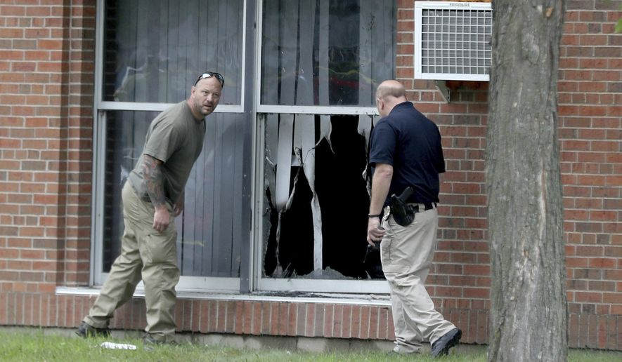 Law enforcement officials investigate an explosion at the Dar Al-Farooq Islamic Center in Bloomington, Minn., on Saturday, Aug. 5, 2017.   Bloomington police Chief Jeff Potts said Saturday that investigators are trying to determine the cause of the blast. Authorities say the explosion damaged one room but it didn't hurt anyone. (David Joles/Star Tribune via AP)