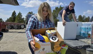 Alaina Browning, left, and Amanda Anderson load Browning's pickup struck with donated food and water to help those still working on the Lodgepole Complex Fire burning in Garfield and Petroleum Counties. As of Thursday the fire was 62 percent contained after burning 270,200 acres. (Rion Sanders/Great Falls Tribune via AP)
