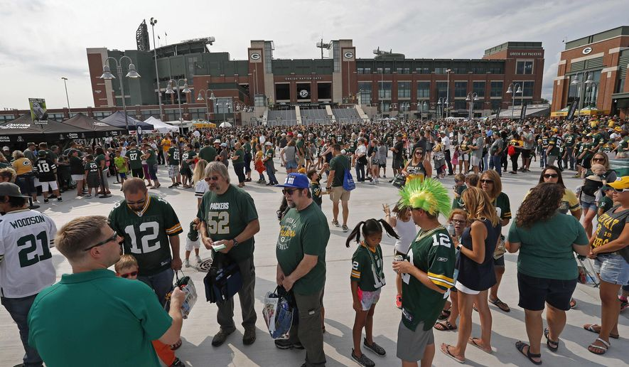 Green Bay Packers fans make their way to Lambeau Field to watch a Packers NFL football training camp practice, Saturday, Aug 5, 2017, in Green Bay, Wis. (AP Photo/Matt Ludtke)