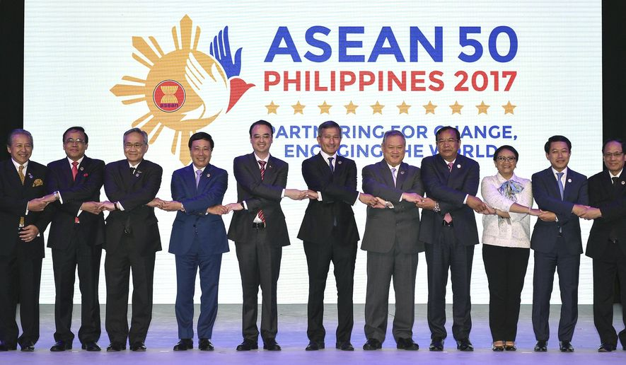 "ASEAN Foreign Ministers link hands ""The ASEAN Way"" at the opening ceremony of the 50th ASEAN Foreign Ministers Meeting at the Philippine International Convention Center Saturday, Aug. 5, 2017 in suburban Pasay city, south of Manila, Philippines. They are, from left, Malaysia's Anifah Aman, Myanmar's U Kyaw Tin, Thailand's Don Pramudwinai, Vietnam's Pham Binh Minh, Philippines' Alan Peter Cayetano, Singapore's Vivian Balakrishnan, Brunei's Lim Jock Seng, Cambodia's Prak Sokhonn, Indonesia's Retno Marsudi, Laos' Saleumxay Kommasith and ASEAN Secretary-General Le Luong Minh. (AP Photo/Mohd Rasfan, Pool)"