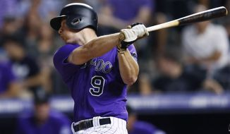 Colorado Rockies' DJ LeMahieu watches his RBI single off Philadelphia Phillies relief pitcher Luis Garcia during the eighth inning of a baseball game Friday, Aug. 4, 2017, in Denver. The Rockies won 4-3. (AP Photo/David Zalubowski)