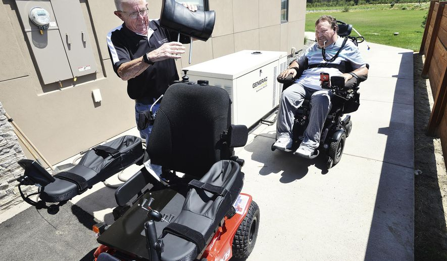 ADVANCE FOR WEEKEND EDITIONS, AUG. 5-6 - In this July 18, 2017 photo, Pete Hedberg, with Pacific Healthcare Associates, puts a head rest on a new all-terrain wheelchair as Nels Hadden watches at his home in Walla Walla, Wash. Hadden was paralyzed nearly nine years ago while helping a motorist on Interstate 84 near Arlington, Ore. (E.J. Harris/East Oregonian via AP)