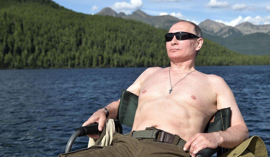 In this photo released by Kremlin press service on Saturday, Aug. 5, 2017, Russian President Vladimir Putin rests after fishing during a mini-break in the Siberian Tyva region, a few days ago. (Alexei Nikolsky/Sputnik, Kremlin Pool Photo via AP)