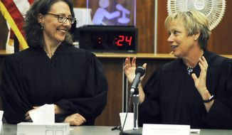 Kenai Superior Court Judge Anna Moran, right, offers congratulations and advice to newly installed Superior Court Judge Jennifer Wells during Wells' installation ceremony Thursday, July 27, 2017, in Kenai, Alaska. Wells, a 27-year veteran of the Alaska court system, replaces former Superior Court Judge Carl Bauman, who retired in February, 2017. (Elizabeth Earl/Peninsula Clarion via AP)