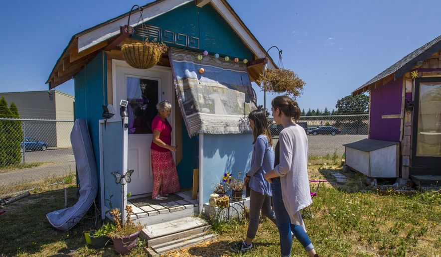 In this Tuesday, July 17, 2017 photo, University of Oregon students Paige Portwood and Samantha Freson meet Alice Gentry for the first time on at Opportunity Village in Eugene, Ore. Portwood and Freson are helping to build Gentry's new tiny home in the Emerald Village that is currently under construction at the corner of N Polk St. and Railroad Blvd in Eugene, Ore. (Rhianna Gelhart/The Register-Guard via AP)