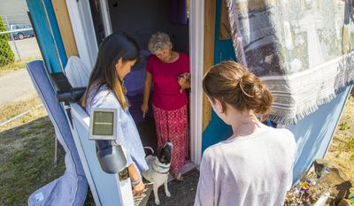 In this Tuesday, July 17, 2017, University of Oregon students Paige Portwood and Samantha Freson meet Alice Gentry for the first time at Opportunity Village in Eugene, Ore. Portwood and Freson are helping to build Gentry's new tiny home in the Emerald Village that is currently under construction at the corner of N Polk St. and Railroad Blvd in Eugene, Ore. (Rhianna Gelhart/The Register-Guard via AP)