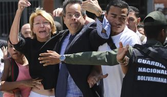 Venezuelan General Prosecutor Luisa Ortega Diaz, left, is surrounded by loyal employees of the General Prosecutor's office, as she was barred from entering by security forces, outside of the General Prosecutor headquarters in Caracas, Venezuela, Saturday, Aug. 5, 2017. Security forces surrounded the entrance ahead of a session of the newly-installed constitutional assembly in which the pro-government body is expected to debate the onetime loyalist turned arch critic's removal. (AP Photo/Wil Riera)