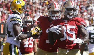 San Francisco 49ers tight end Vernon Davis (85) and quarterback Colin Kaepernick, center, celebrate after connecting on a two-yard touchdown pass next to Green Bay Packers cornerback Jarrett Bush during the third quarter of after an NFL football game in San Francisco, Sunday, Sept. 8, 2013. (AP Photo/Ben Margot)