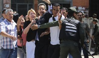 Venezuelan General Prosecutor Luisa Ortega Diaz, third left, is surrounded by loyal employees of the General Prosecutor's office, as she was barred from entering her office by security forces, outside of the General Prosecutor headquarters in Caracas, Venezuela, Saturday, Aug. 5, 2017. Security forces surrounded the entrance ahead of a session of the newly-installed constitutional assembly in which the pro-government body is expected to debate the onetime loyalist turned arch critic's removal. (AP Photo/Wil Riera)