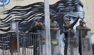 Venezuelan Bolivarian National Guards officers lineup outside of General Prosecutor headquarters in Caracas, Venezuela, Saturday, Aug. 5, 2017. Security forces surrounded the entrance to Venezuela's chief prosecutor's office early Saturday ahead of a session of the newly-installed constitutional assembly in which the pro-government body is expected to debate the onetime loyalist turned arch critic's removal. (AP Photo/Ariana Cubillos)