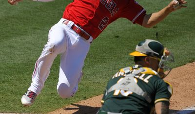 Los Angeles Angels' Andrelton Simmons, top, scores on a single by Kole Calhoun as Oakland Athletics catcher Bruce Maxwell takes a late throw during the fifth inning of a baseball game, Sunday, Aug. 6, 2017, in Anaheim, Calif. (AP Photo/Mark J. Terrill)