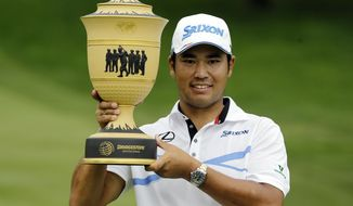 Hideki Matsuyama, from Japan, holds up The Gary Player Cup trophy after the final round of the Bridgestone Invitational golf tournament at Firestone Country Club, Sunday, Aug. 6, 2017, in Akron, Ohio. Matsuyama finished the tournament at 16-under par. (AP Photo/Tony Dejak)