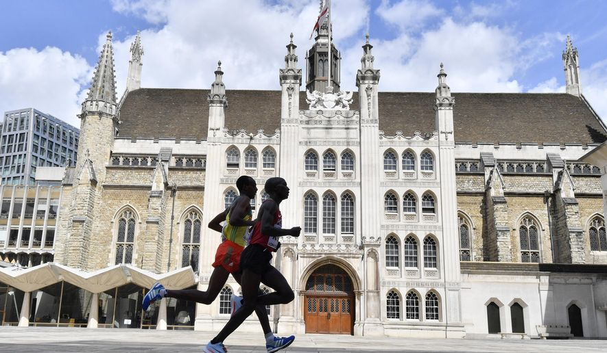Kenya's Geoffrey Kipkorir Kirui, right, leads Ethiopia's Tamirat Tola past the Guildhall on his way to winning the gold medal in the Men's Marathon during the World Athletics Championships Sunday, Aug. 6, 2017. (AP Photo/Martin Meissner)