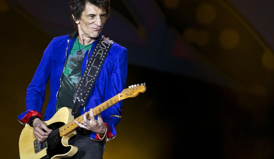 """FILE - In this file photo dated Friday March 25, 2016, Rolling Stones guitarist Ron Wood performs during a Rolling Stones concert in Havana, Cuba.  In an interview published in a British newspaper Sunday Aug. 6, 2017,  70-year old Wood reveals that he recently underwent an emergency operation after being diagnosed with lung cancer, and quoted as saying """"There was a week when everything hung in the balance and it could have been curtains - time to say goodbye.""""  A doctor made the cancer diagnosis when the former hellraiser underwent routine health tests before the upcoming Rolling Stones tour. (AP Photo/Enric Marti, FILE)"""