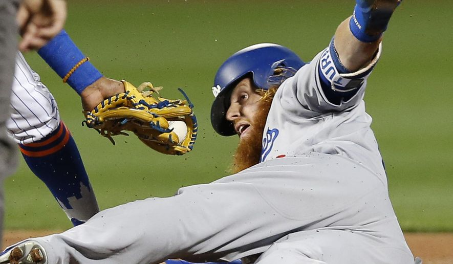 Los Angeles Dodgers' Justin Turner reaches around the tag of New York Mets shortstop Amed Rosario for stolen base during the first inning of a baseball game Sunday, Aug. 6, 2017, in New York. Turner was called out on the play by second base umpire Will Little, but the call on the field was overruled by the Dodgers' manager's challenge. (AP Photo/Kathy Willens)