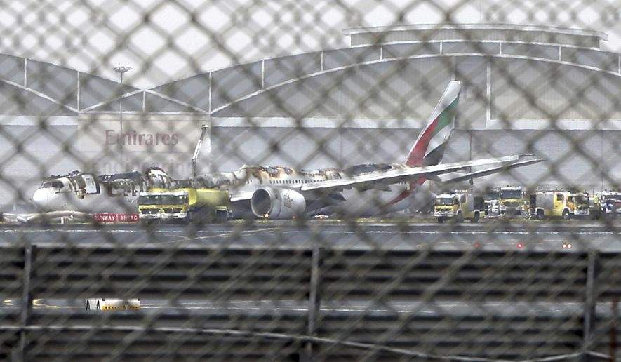 "FILE- In this Wednesday, Aug 3, 2016 file photo, a damaged Boeing 777 is seen at the Dubai airport after it crash-landed, in Dubai, United Arab Emirates. Investigators said Sunday no mechanical issues affected an Emirates flight before it crash landed in Dubai and burst into flames last year, as their probe continues to look at ""human performance factors"" around the inciden. (AP Photo/Jon Gambrell, file)"