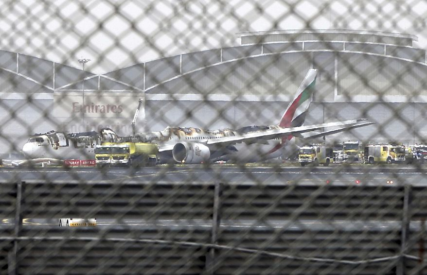 """FILE- In this Wednesday, Aug 3, 2016 file photo, a damaged Boeing 777 is seen at the Dubai airport after it crash-landed, in Dubai, United Arab Emirates. Investigators said Sunday no mechanical issues affected an Emirates flight before it crash landed in Dubai and burst into flames last year, as their probe continues to look at """"human performance factors"""" around the inciden. (AP Photo/Jon Gambrell, file)"""