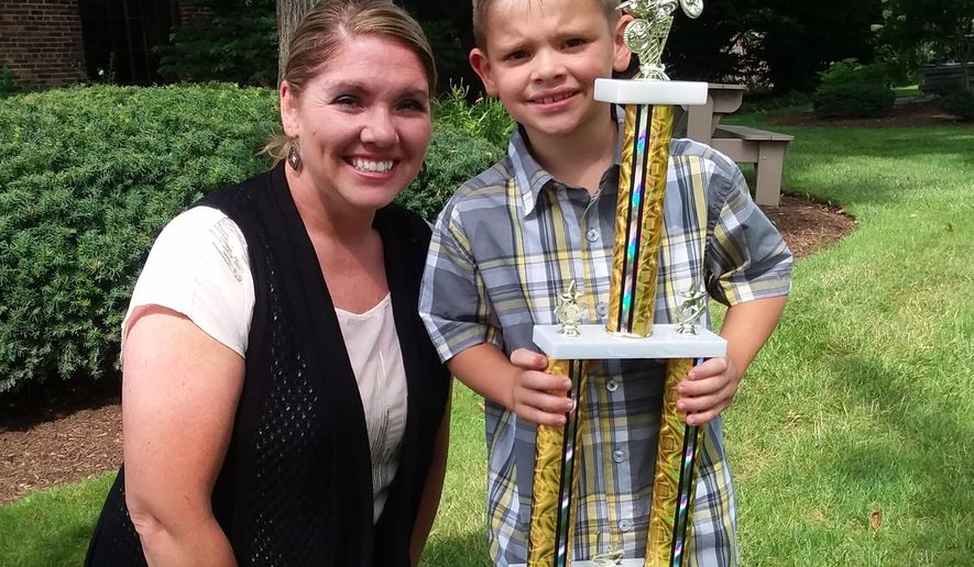 In this undated photo, Isaac Williamson and his mom, Andrea, pose with one of his trophies. The 7-year-old from Lexington Township near Alliance, Ohio, is a state motocross champion and is looking to race more in the future. (Charita Goshay/The Canton Repository via AP)