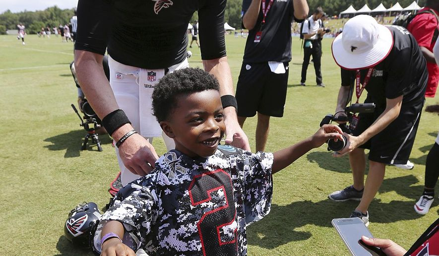 Atlanta Falcons quarterback Matt Ryan gives Anthony Beecher, 6, his jersey at the end of team football practice during Military Day on Sunday, August 6, 2017, in Flowery Branch, Ga. Beecher's father, U.S. Army Staff Sergeant Michael Beecher, is deceased. (Curtis Compton/Atlanta Journal-Constitution via AP)