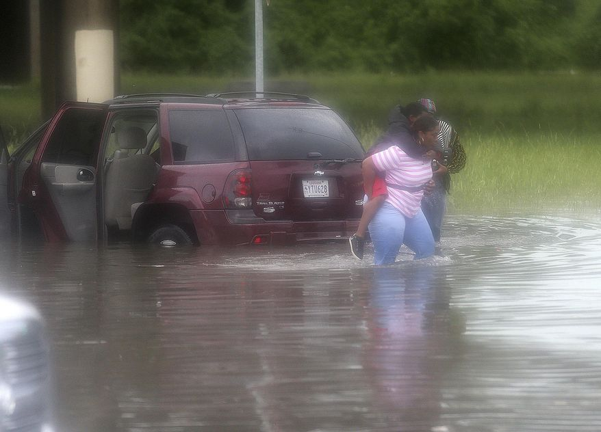 A woman carries a child from a flooded car at the Franklin Ave. I-610 exit as a torrential downpour flooded city streets, Saturday, Aug. 5, 2017 in New Orleans. Officials in New Orleans say heavy rainfall overwhelmed the city's pump stations, contributing to flooding in some areas. (Michael DeMocker/NOLA.com The Times-Picayune via AP)