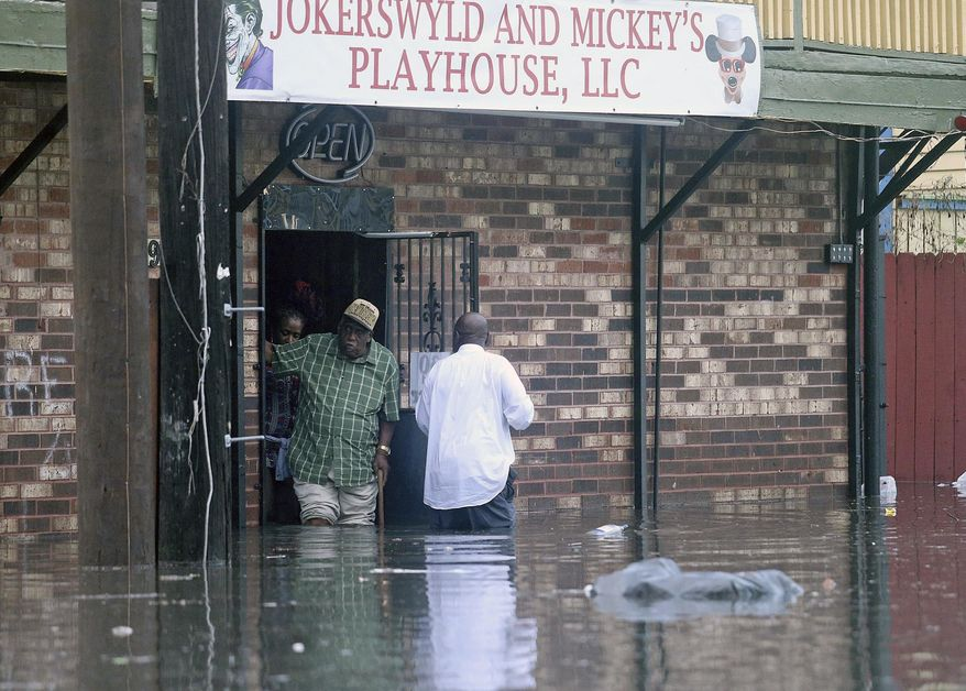 Patrons emerge from a flooded club on Orleans Ave. after a torrential downpour flooded city streets, Saturday, Aug. 5, 2017 in New Orleans. Officials in New Orleans say heavy rainfall overwhelmed the city's pump stations, contributing to flooding in some areas. (Michael DeMocker/NOLA.com The Times-Picayune via AP)