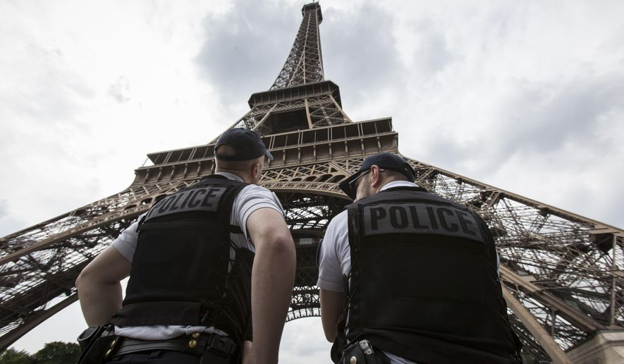 FILE- In this Friday, June 10, 2016 file photo, French riot police officers patrol under the Eiffel Tower, in Paris. A young French man who recently was discharged from a psychiatric hospital is under investigation for glorifying terrorism after he brandished a knife and tried to breach security at the Eiffel Tower, authorities said Sunday, Aug. 6, 2017. (AP Photo/Kamil Zihnioglu, File)
