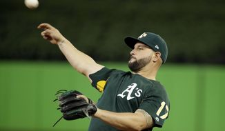 FILE - This  June 13, 2017 file photo shows Oakland Athletics first baseman Yonder Alonso (17) throwing during batting practice before an interleague baseball game against the Miami Marlins in Miami. The Seattle Mariners acquired Alonso from the Athletics on Sunday, Aug. 6, 2017 for minor league outfielder Boog Powell. (AP Photo/Lynne Sladky, file)