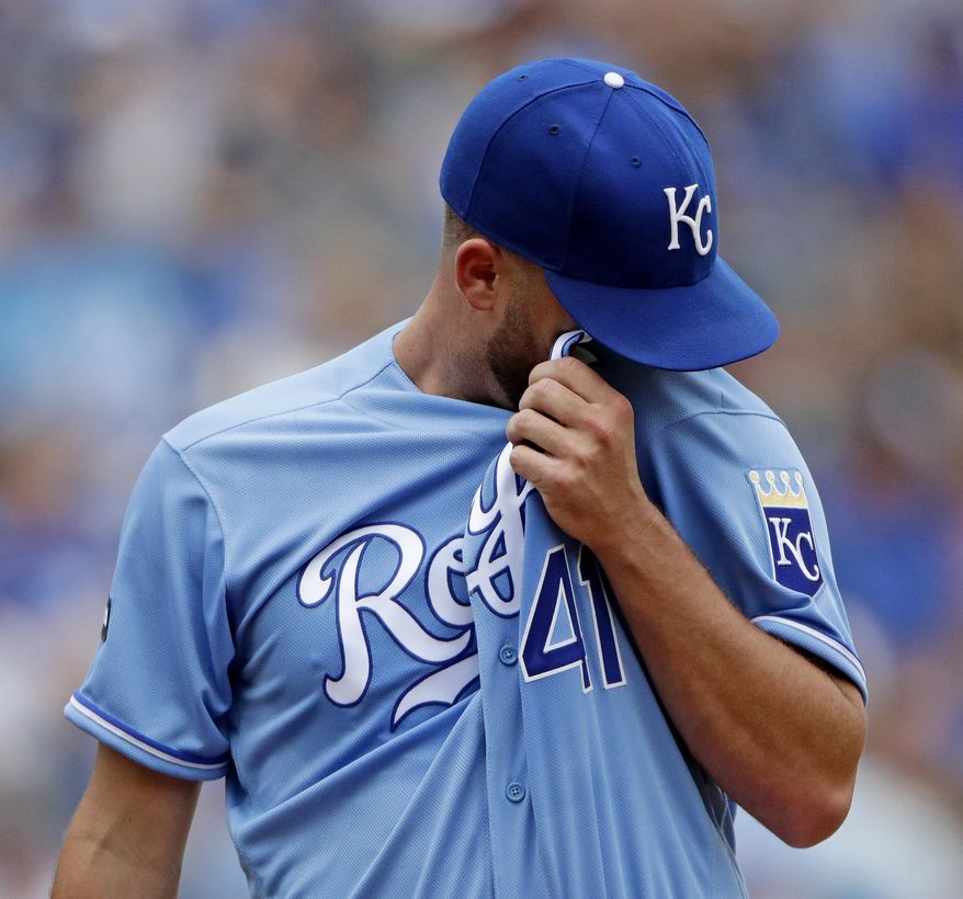 Kansas City Royals starting pitcher Danny Duffy wipes away sweat during the first inning of the first baseball game of a doubleheader against the Seattle Mariners Sunday, Aug. 6, 2017, in Kansas City, Mo. (AP Photo/Charlie Riedel)