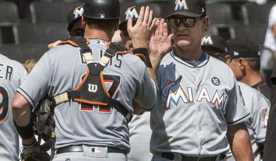 Miami Marlins manager Don Mattingly, right, congratulates catcher A.J. Ellis (17) after a baseball game against the Atlanta Braves, Sunday, Aug. 6, 2017, in Atlanta. (AP Photo/John Amis)