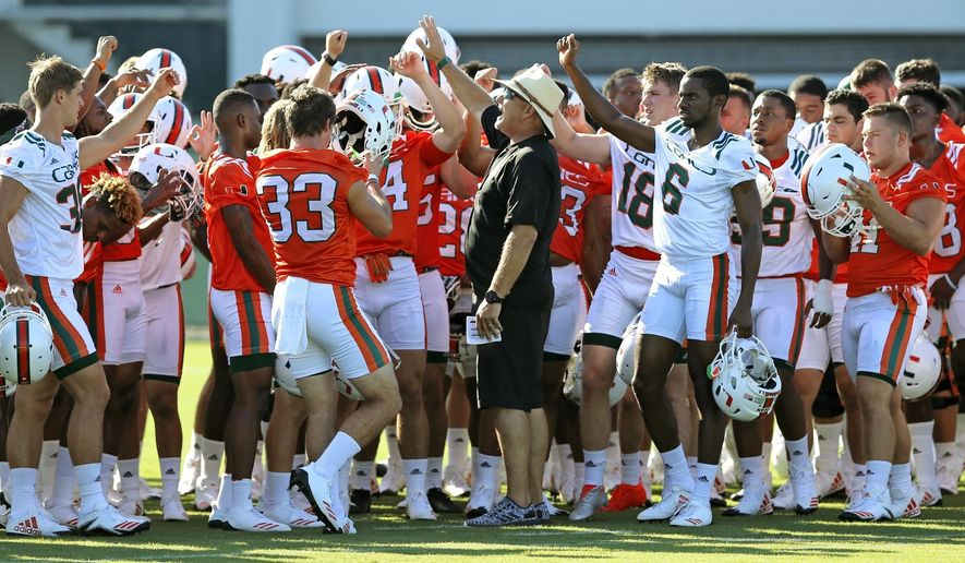 University of Miami NCAA college football team head coach Mark Richt, center, huddles with players at practice in Coral Gables, Fla., Wednesday, Aug. 2, 2017. (Al Diaz/Miami Herald via AP)