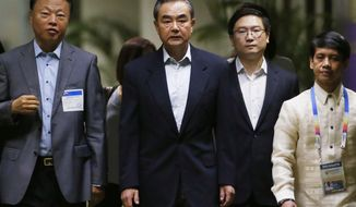 Chinese Foreign Minister Wang Yi, center, is escorted by Chinese Ambassador to the Philippines Zhao Jianhua, left, upon arrival to take part in the 50th ASEAN Foreign Ministers' Meeting and its Dialogue Partners, Saturday, Aug. 5, 2017, in suburban Pasay city south Manila, Philippines.  Alarm over North Korea's missile tests, a tentative step to temper South China Sea disputes, and unease over a disastrous siege by pro-Islamic State group militants, will grab the spotlight at the annual meetings of Southeast Asia's top diplomats and their Asian and Western counterparts. (AP Photo/Bullit Marquez)