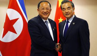 North Korean Foreign Minister Ri Yong Ho, left, poses with his Chinese counterpart Wang Yi for a photo prior to their bilateral meeting in the sideline of the 50th ASEAN Foreign Ministers' Meeting and its Dialogue Partners. Sunday, Aug. 6, 2017 in suburban Pasay city, south Manila, Philippines. Bolstered by new U.N. sanctions, the United States and North Korea's neighbors are joining in a fresh attempt to isolate Pyongyang over its nuclear and missile programs, in a global campaign cheered on by U.S. President Donald Trump. (AP Photo/Bullit Marquez)