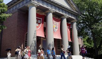 In this Aug. 30, 2012, file photo, a tour group walks through the campus of Harvard University in Cambridge, Mass. (AP Photo/Elise Amendola, File) **FILE**