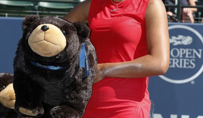 Madison Keys, of the United States, holds a stuffed bear after defeating Coco Vandeweghe, of the United States, during the finals of the Bank of the West Classic tennis tournament in Stanford, Calif., Sunday, Aug. 6, 2017. Keys won 7-6, 6-4. (AP Photo/Tony Avelar)