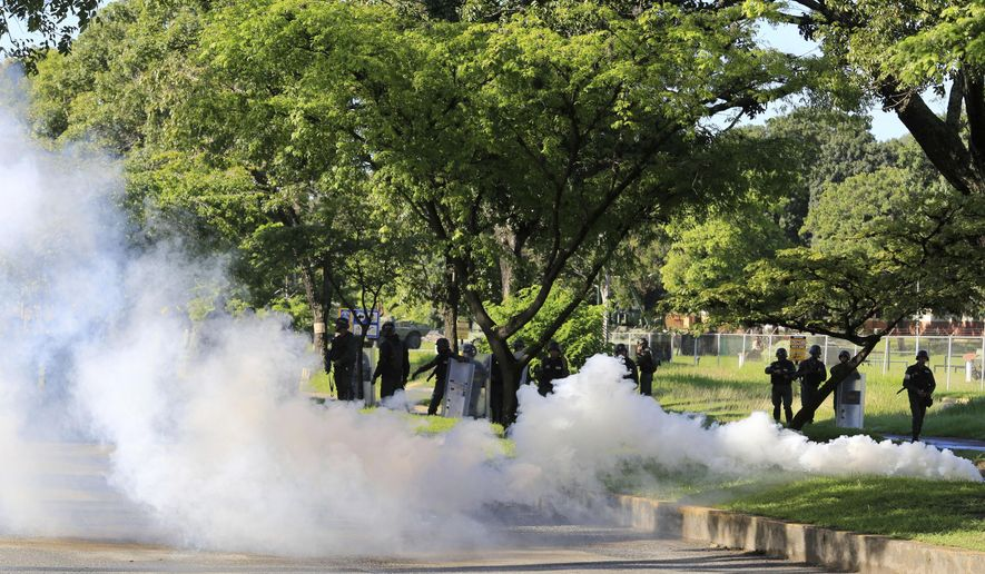 "Venezuelan Bolivarian National Guard officers fire teargase towards resident that try to walks to the Military base Paramacay in Valencia, Venezuela, Sunday Aug. 6, 2017. Venezuelan ruling party chief Diosdado Cabello said the military squashed a ""terrorist"" attack at the military base Sunday, shortly after a small group of men dressed in military fatigues released a video declaring themselves in rebellion. (AP Photo/Juan Carlos Hernandez)"