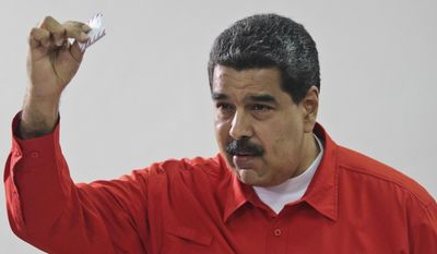 Venezuela's President Nicolas Maduro shows his ballot after casting a vote for a constitutional assembly in Caracas, Venezuela, July 30. (Miraflores Press Office via AP) ** FILE **