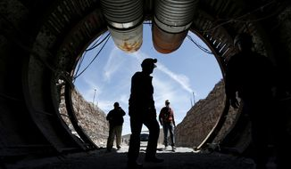 FILE - In this April 9, 2015, file photo, people walk into the south portal of Yucca Mountain during a congressional tour of the proposed radioactive waste dump near Mercury, Nev., 90 miles northwest of Las Vegas. Nevada wants a federal appeals court to dismiss a bid by the state of Texas to kick-start government funding and licensing for a long-fought plan to entomb the nation's most radioactive waste in the desert outside Las Vegas. (AP Photo/John Locher, File)