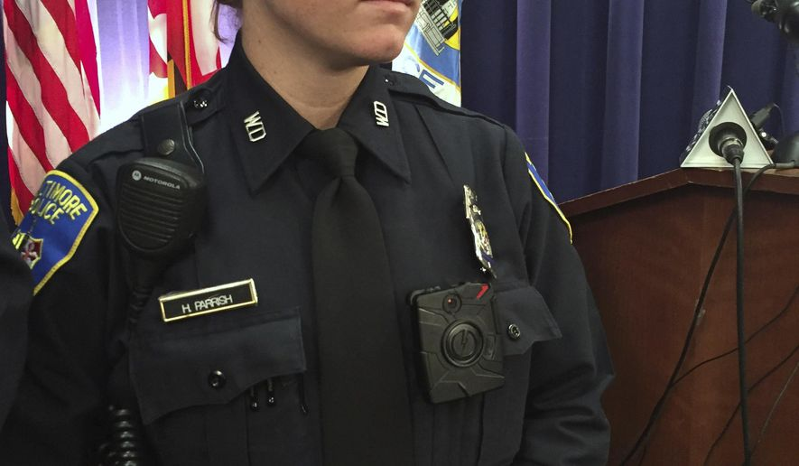 File-This Oct. 26, 2015, file photo shows Officer Hannah Parish displaying a Taser International Axon Camera body camera during a news conference  in Baltimore. The Baltimore Police Department is having a tough time restoring public confidence in the troubled agency. The city is on pace to break its decades-old murder record and the body camera program that was rolled out to increase transparency has fueled allegations of misconduct after a pair of problematic videos recently surfaced. (AP Photo/Juliet Linderman, File)
