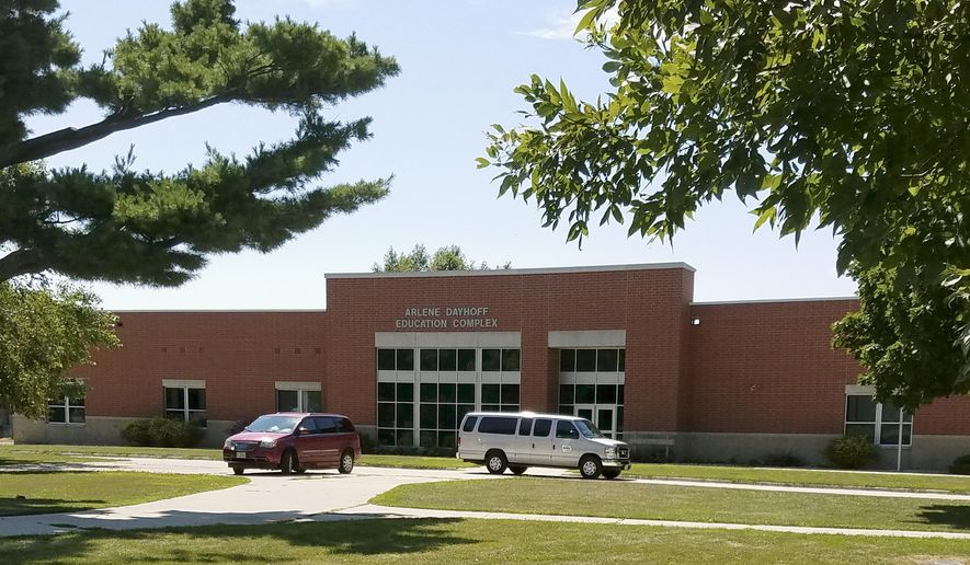 In this photo provided by the State of Iowa, vehicles are parked out the entrance to the Arlene Dayhoff Education Complex at the Boys State Training School in Eldora, Iowa, Monday, Aug. 7, 2017. A federally funded nonprofit organization claims in a report released Monday that the school for juvenile boys held under court order is violating their constitutional rights by not providing essential mental health care and instead relying on restraints and seclusion rooms, and the group is threatening legal action unless the state makes significant changes. (State of Iowa via AP)