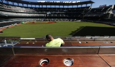 FILE - In this March 9, 2017, file photo, cup holders designed to keep drinks cold line an outfield viewing section at SunTrust Park, the Atlanta Braves' new baseball stadium, in Atlanta. On hot days fans can take advantage of the refrigerated drinker coolers that are one of the new additions at SunTrust Park. (AP Photo/David Goldman, File)