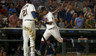 Minnesota Twins Eddie Rosario scores and celebrates the run with Jason Castro after drawing a balk from Milwaukee Brewers relief pitcher Oliver Drake in the seventh inning of a baseball game, Monday, Aug. 7, 2017, in Minneapolis. (AP Photo/Bruce Kluckhohn)