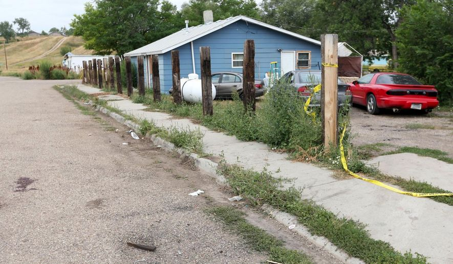 In this Saturday, Aug. 5, 2017, photo, crime scene tape surrounds a property in Lodge Grass, Mont. Drugs and gang activity were factors in a residential shooting that killed multiple people and injured others on Friday on Montana's Crow Indian Reservation, the tribe's chairman said. (Casey Page/The Billings Gazette via AP)