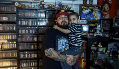 Nick Rodriguez and his son, Maximus, 3, browses some of his dad's games inside his home in Irwin on Wednesday, May 24, 2017. Rodriguez, the 33-year-old collector, who kept a Nintendo collection worth thousands in a closet in his Irwin home decided this week to sell it all to Warp Zone, a video game store in Greensburg. (Nate Smallwood/Pittsburgh Tribune-Review via AP)