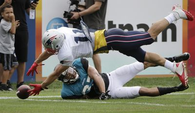 New England Patriots wide receiver Julian Edelman, top, reaches for the ball as Jacksonville Jaguars defensive back Tyler Patmon, below, tries to defend during an NFL football joint practice, Monday, Aug. 7, 2017, in Foxborough, Mass. (AP Photo/Steven Senne)