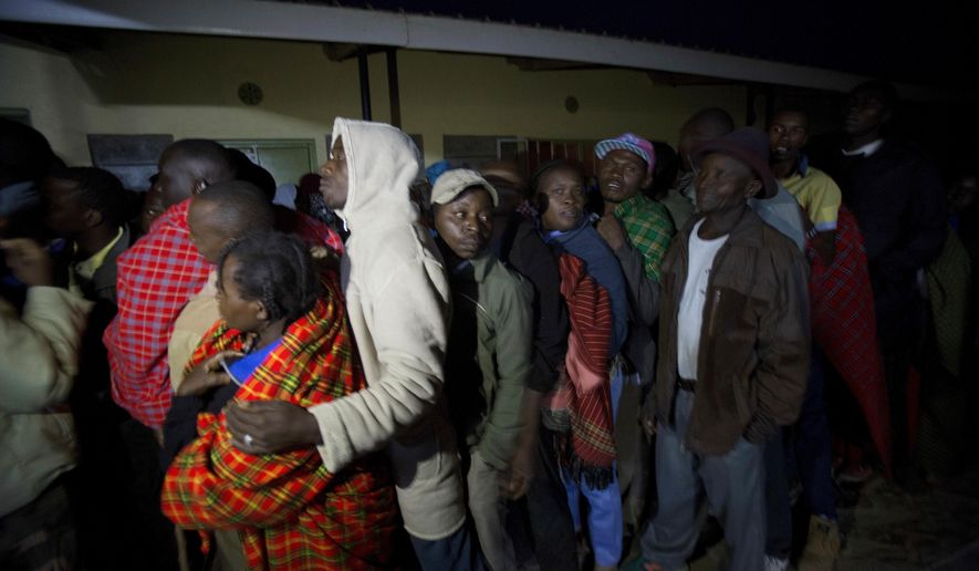 Maasai men line up before the opening of the polling stations in Bissil, 120 kilometers (74.5 miles) south of Nairobi, Kenya, Tuesday, Aug. 8, 2017. Kenyans are going to the polls to vote in a general election after a tightly-fought presidential race between incumbent President Uhuru Kenyatta and main opposition leader Raila Odinga. (AP Photo/Jerome Delay)